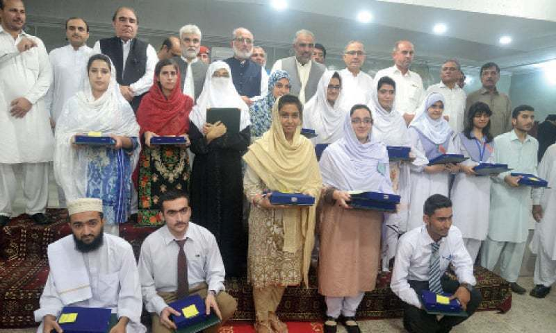 Khyber Pakhtunkhwa Assembly Speaker Asad Qaiser and officials of Board of Intermediate and Secondary Education Peshawar pose for a group photo with position holders in Peshawar on Saturday. — White Star