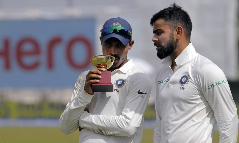 Ravindra Jadeja holds the Man of the Match trophy as he listens to team captain Virat Kohli after their win over Sri Lanka in their second cricket test match in Colombo. —AP