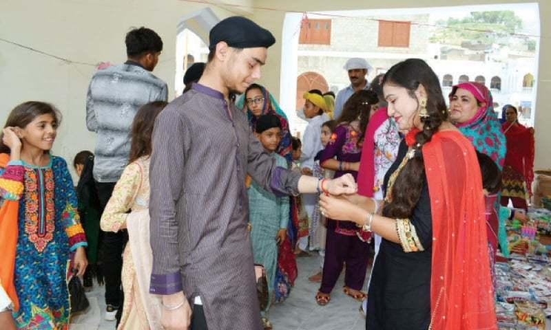 Arooj Kumari from Kohat ties Rakhi on the wrist of Harjeet Singh, a resident of Hassanabdal, at Gurdwara Punja Sahib on Monday. — Dawn