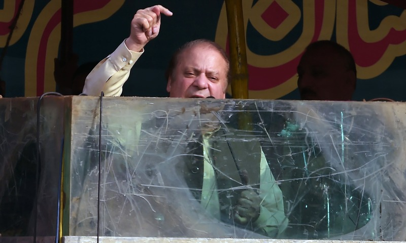 Nawaz Sharif speaks behind a bullet-proof glass during a rally in Gujrat. Photo:AFP