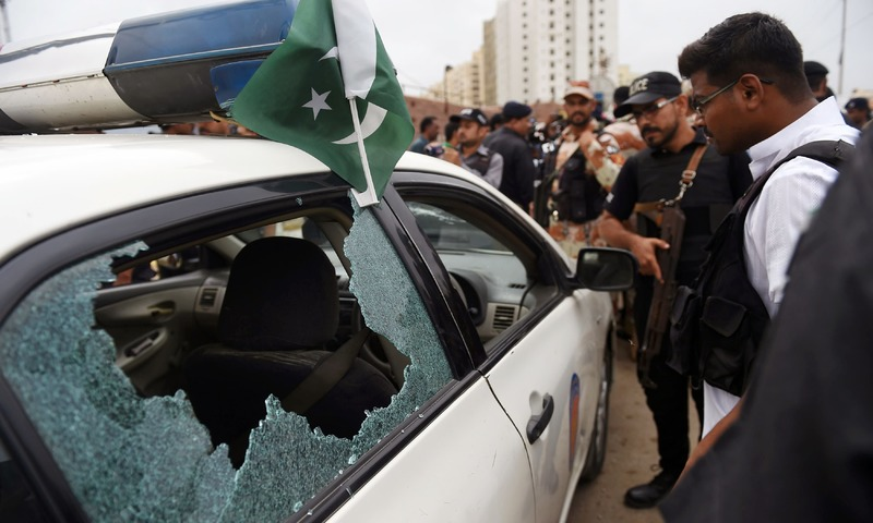 Investigators inspect a police vehicle after it was attacked by gunmen in Karachi. —AFP
