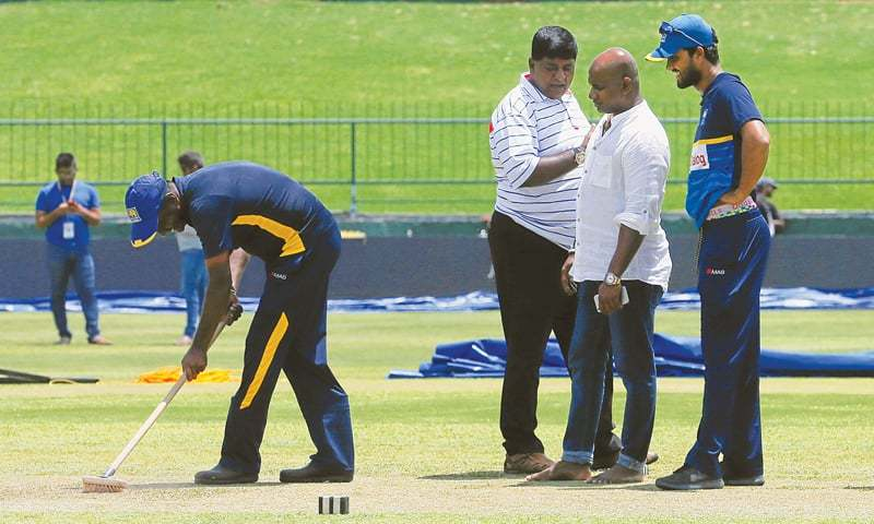 Sri Lankan captain Dinesh Chandimal (R) and chairman of selection committee Sanath Jayasuriya inspect the pitch at the Pallekele International Cricket Stadium on Friday ahead of the final Test against India.— Reuters
