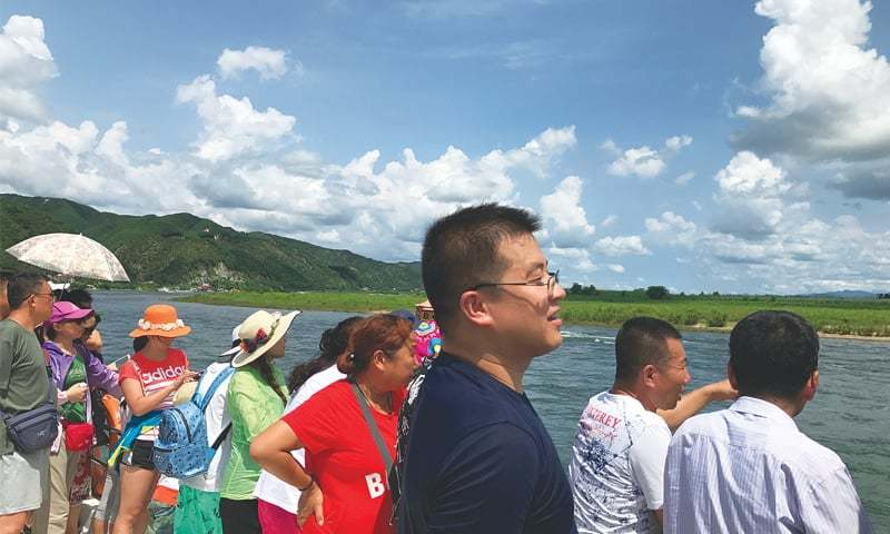 Dandong (Liaoning province, China): Chinese tourists are seen on a boat taking them from the Chinese side of the Yalu River for sightseeing close to the shores of North Korea on Thursday.—Reuters