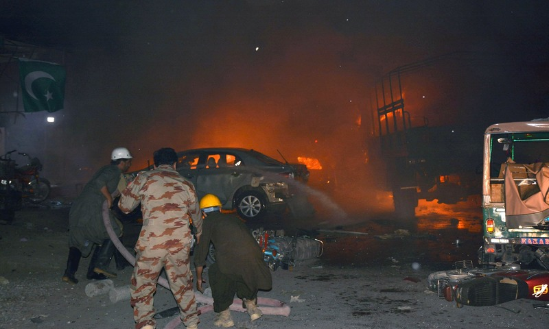 Firefighters use hoses to try to extinguish burning vehicles after a blast in Quetta. —AFP