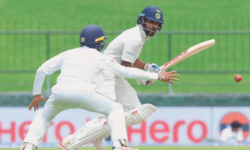 PALLEKELE: Indian opener Shikhar Dhawan takes another run during his century knock as Sri Lanka fielder Kusal Mendis attempts to stop the ball during the third Test at the Pallekele International Cricket Stadium on Saturday.─AFP