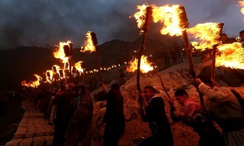 Iraqi Kurdish people carry fire torches up a mountain where a giant flag of Iraq's autonomous Kurdistan region is laid, as they celebrate Newroz Day, a festival marking their spring and new year, in the town of Akra, Iraq March 20, 2016. ─Reuters/File