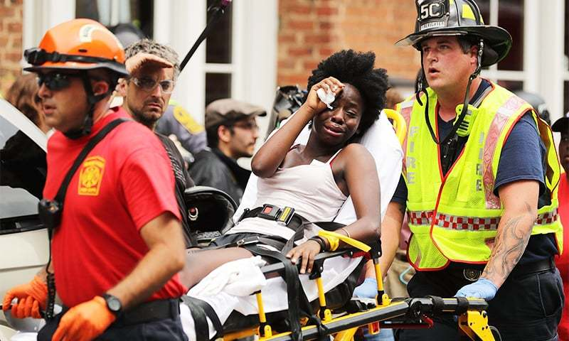 Rescue workers move victims on stretchers after a car plowed through a crowd of counter-demonstrators marching through the downtown shopping district. ─ AFP