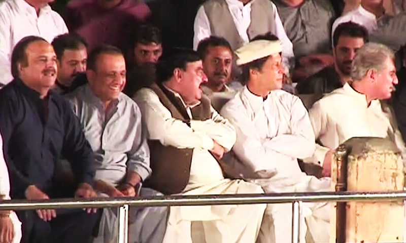PTI chief Imran Khan and AML head Sheikh Rashid on stage at Liaquat Bagh.—DawnNews