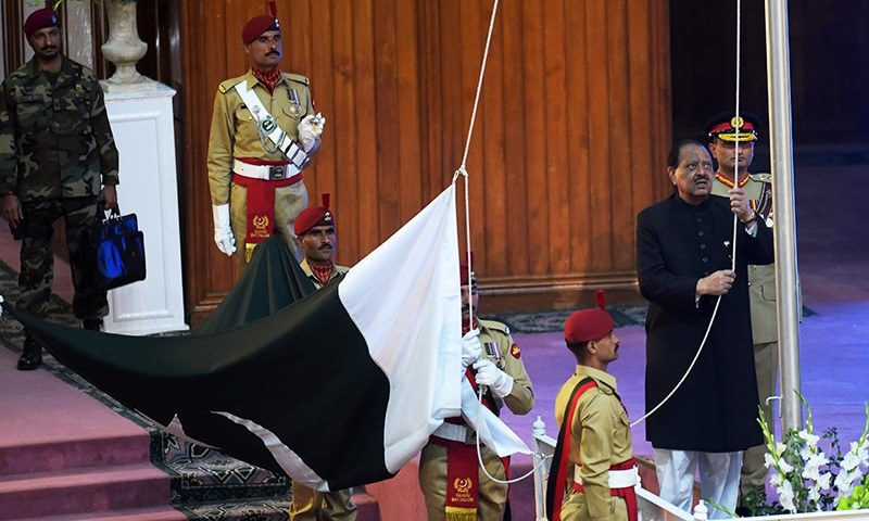President Mamnoon Hussain (R) hoists the national flag during a ceremony to mark the country's Independence Day in Islamabad.— AFP