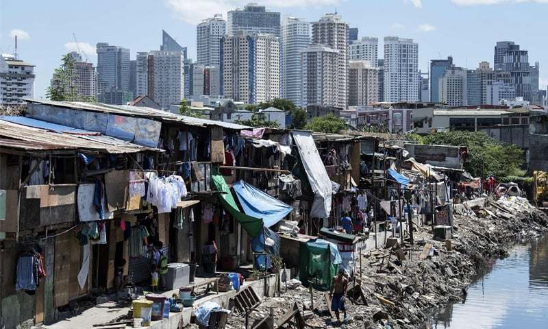 People living in a settlement walk about, as the skyline of Manila's financial district is seen in the background, on Thursday.—AFP