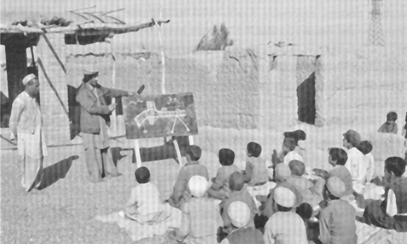 In a photograph dated 1984, children sit on the ground at a madressah in Afghanistan, learning the finer points of the anatomy of what appears to be a gun | Photo from the book