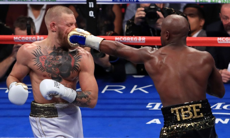 Floyd Mayweather Jr. throws a punch at Conor McGregor during their super welterweight boxing match at T-Mobile Arena in Las Vegas, Nevada. —AFP
