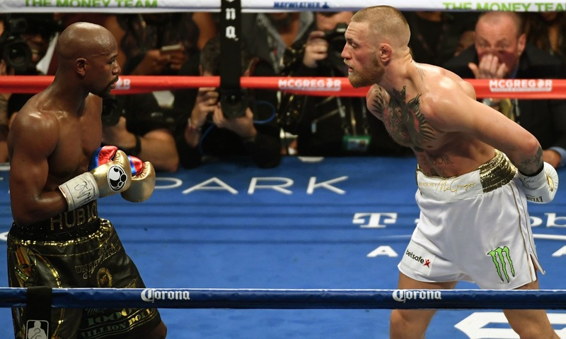 Conor McGregor taunts Floyd Mayweather Jr. during their super welterweight boxing match. —AFP