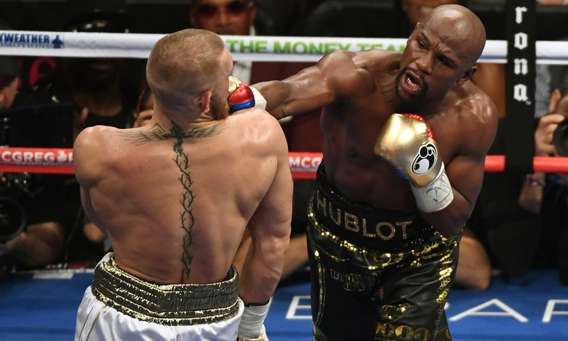 Mayweather Jr. throws a punch at McGregor during their super welterweight boxing match. —AFP
