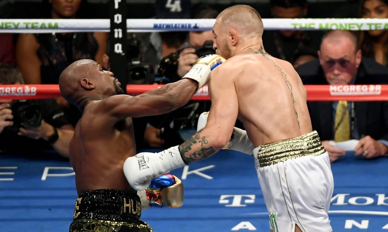 Mayweather Jr. throws a punch at McGregor during their super welterweight boxing match at T-Mobile Arena in Las Vegas, Nevada. —AFP