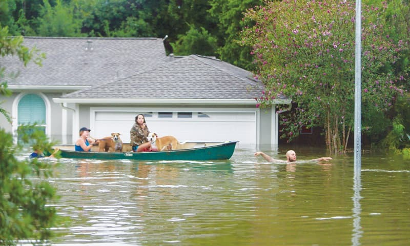HOUSTON: A family leaving their flooded home here on Sunday.—AP