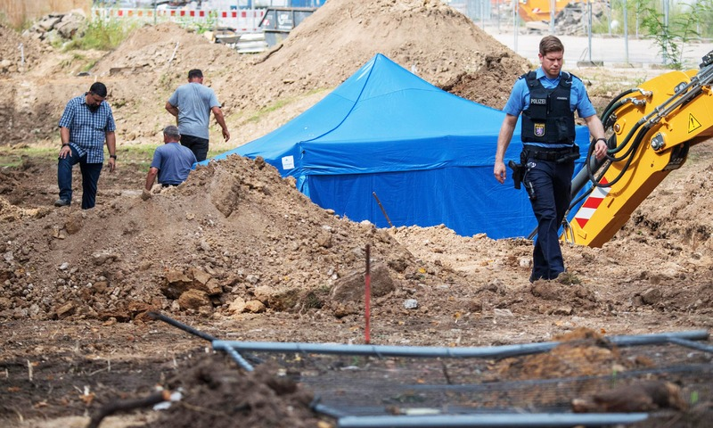 A policeman walks past a blue tent covering a British World War II bomb that was found during construction works on August 30, 2017 in Frankfurt am Main, western Germany. —AFP