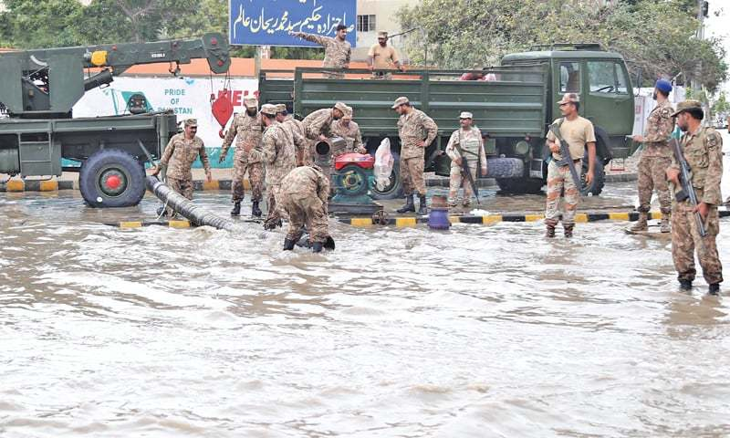ACROSS the city, scenes of devastation were widespread in the wake of the rains on Thursday. Pak Army jawans help drain rainwater at Ayesha Manzil.—Agencies