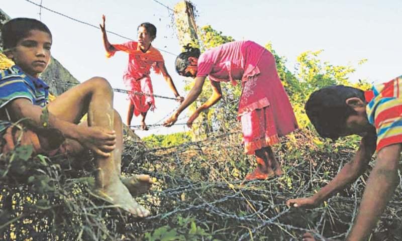 Rohingya children cross the Bangladesh-Myanmar border fence as they try to enter Bangladesh on Aug 29.
