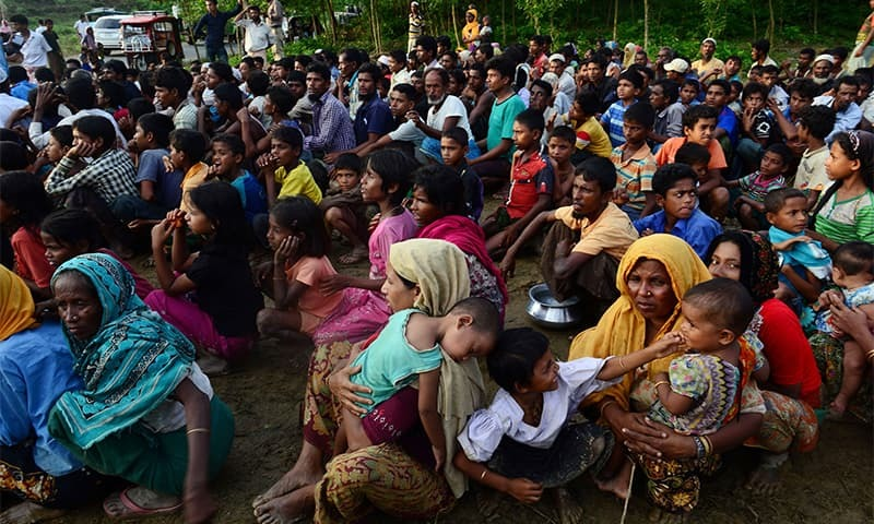 Rohingya people wait for relief supplies near a refugee camp in Kutupalong in the Bangladeshi district of Ukhia.— AFP