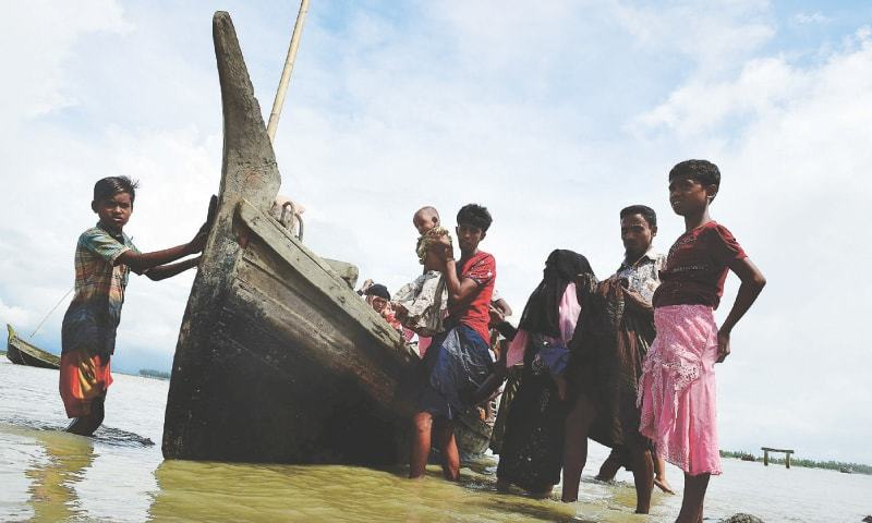 Rohingya Muslim refugees disembark from a boat on the Bangladeshi side of the River Naf in Teknaf on Tuesday.—AFP
