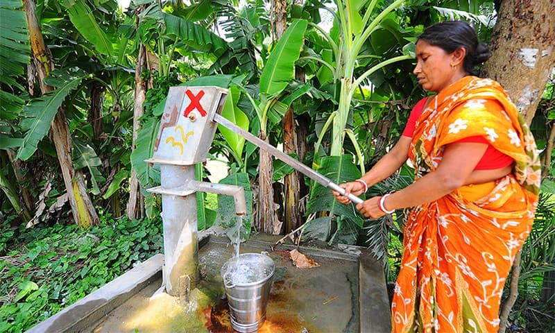A woman pumps up water from a tubewell in West Bengal despite the red cross that signifies that there is an unacceptable level of arsenic in the water.— Photo by The Third Pole