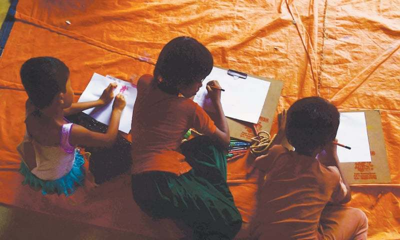 ROHINGYA Muslim children draw pictures at a 'safe house' in Kutupalong refugee camp in the Bangladeshi town of Teknaf on September 11.—AFP