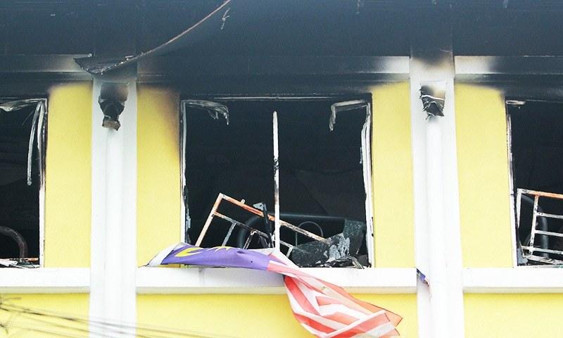 A Malaysian national flag flutters outside burnt windows of the Darul Quran Ittifaqiyah religious school in Kuala Lumpur.—AFP