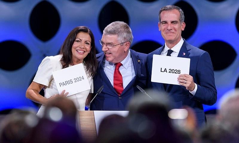 اولمپکس 2024 اور 2028 کے میزبان شہروں کے ناموں کے اعلان کے بعد انٹرنیشنل اولمپکس کمیٹی کے سربراہ تھامس باک لاس اینجلس اور پیرس کے میئرز ساتھ— فوٹو: اے ایف پی