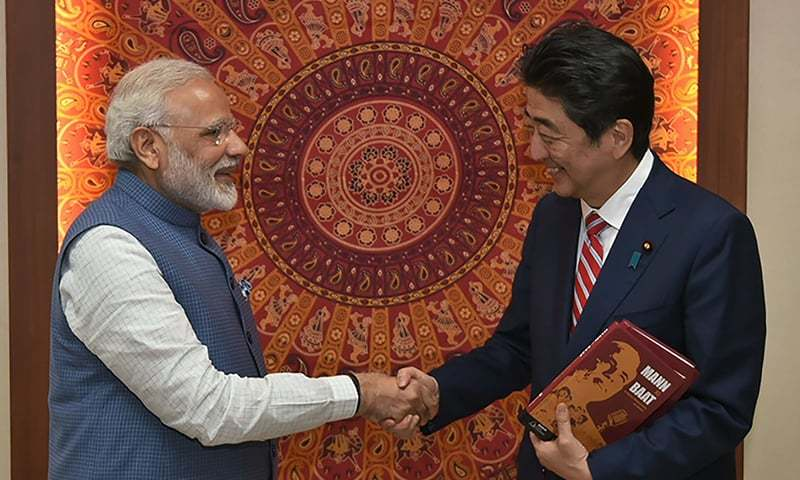 Indian Prime Minister Narendra Modi shakes hands with Japan's Prime Minister Shinzo Abe after presenting him with the book 'Mann Ki Baat - A Social Revolution on Radio'.─AFP