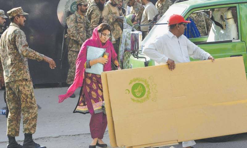 LAHORE: Military personnel and civilian staff on Saturday carry election material from the ECP office to polling stations for the NA-120 by-election.—M. Arif / White Star