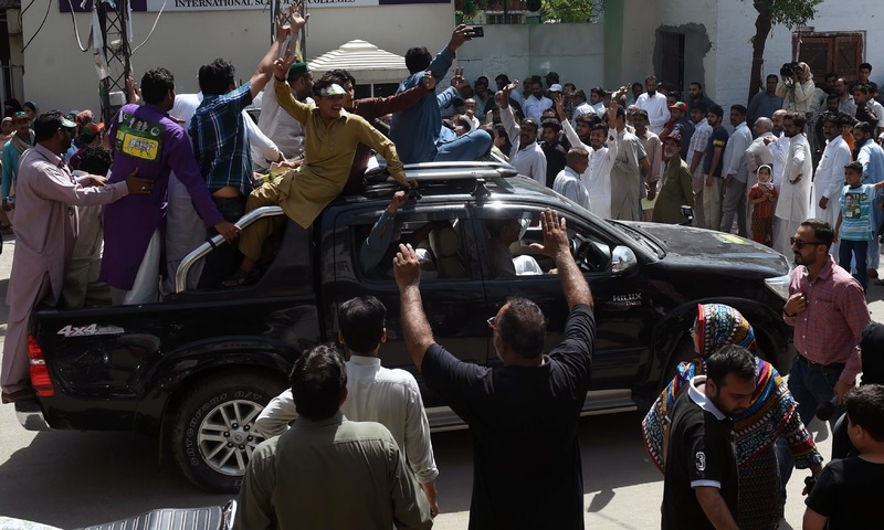 PML-N supporters shout slogans outside a polling station as voting takes place in Lahore. —AFP
