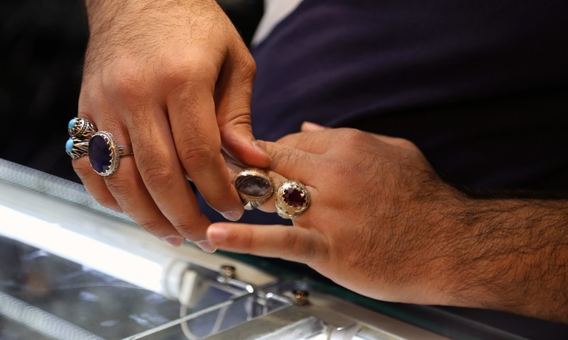 A jeweller tries on a ring at a shop in the main market of Iraq's holy city of Najaf. —AFP