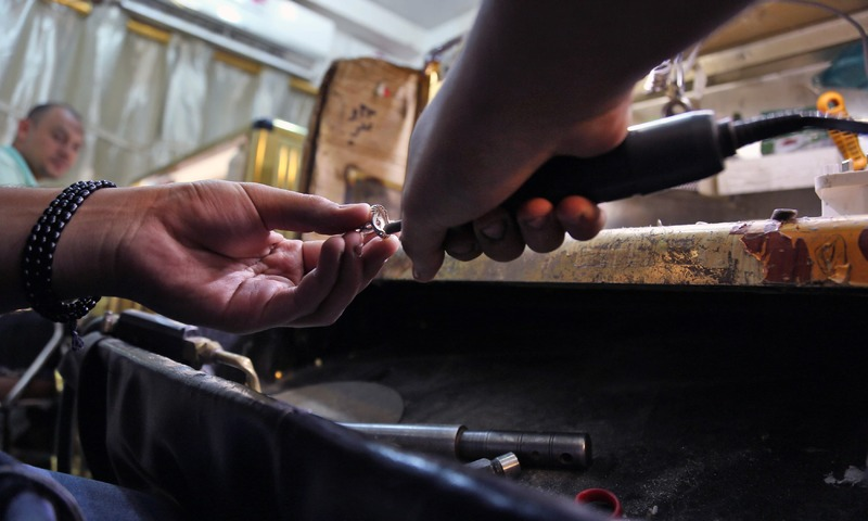 A jeweller fabricates a ring in a workshop in the main market of Iraq's holy city of Najaf. —AFP