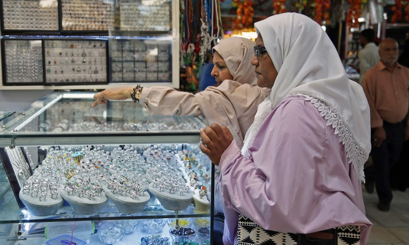 Women browse for rings at a stall outside a jeweller's shop in the main market of Najaf. —AFP