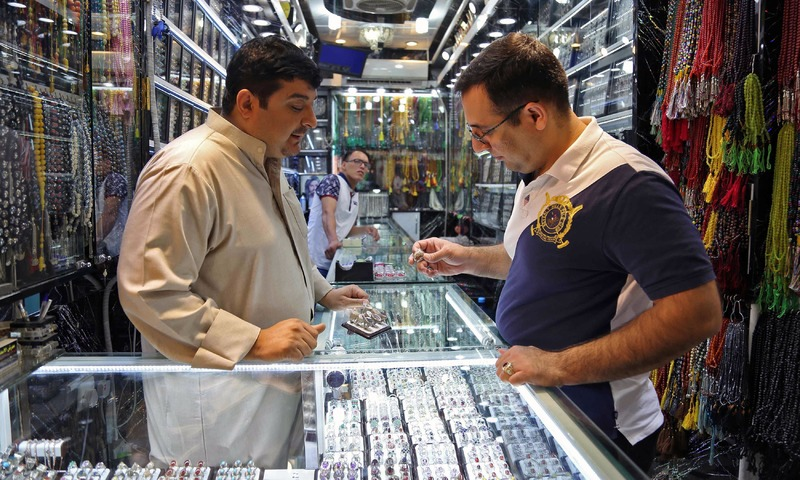 A man browses for rings at a jeweller's in the main market. —AFP