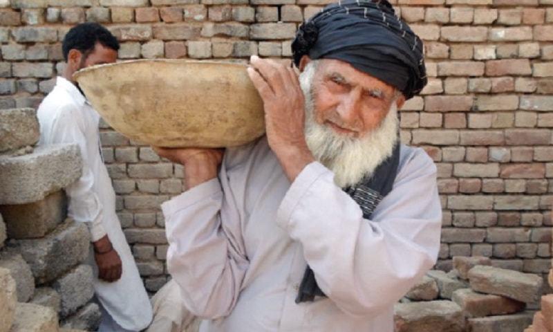 An elderly labourer works at a construction site in Peshawar. —Dawn