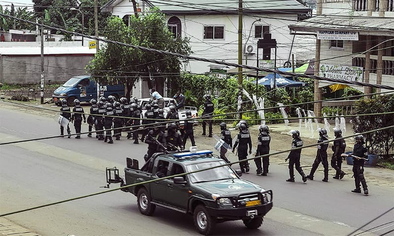 Cameroon police officials with riot equipment patrol along a street in the administrative quarter of Buea some 60kms west of Douala on October 1. — AFP