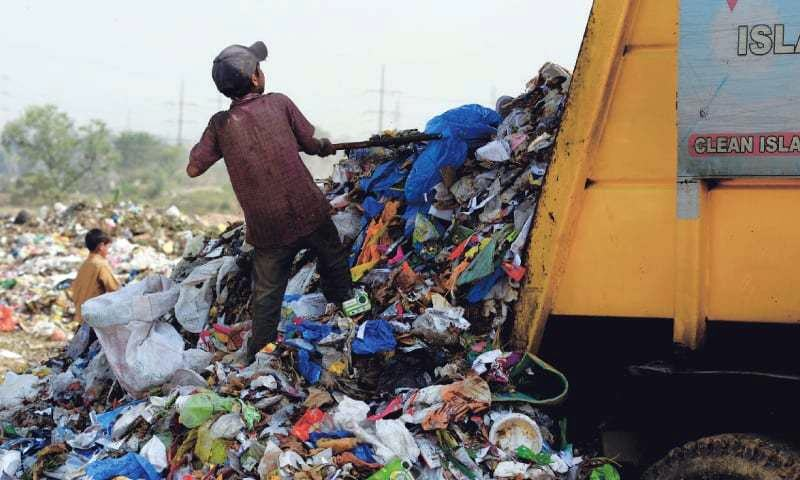 A young rag-picker unloads a truckload of waste at Islamabad's I-12 landfill. Photo by Mohammad Asim/White Star