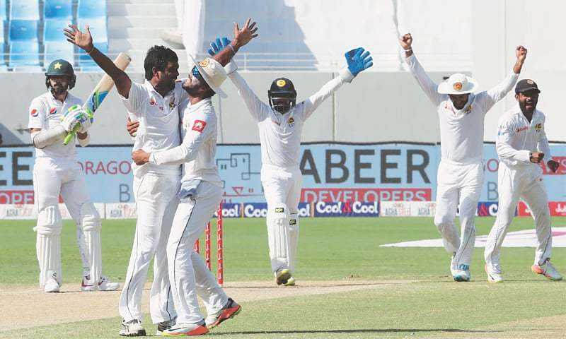 DUBAI: Sri Lankan cricketers celebrate the dismissal of Pakistan's Mohammad Amir during the second Test at the Dubai International Cricket Stadium  on Tuesday.—AFP