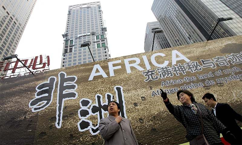 Chinese women stand in front of a billboard which promotes the then upcoming China-Africa summit meeting, outside a hotel in Beijing in this Oct 26, 2006 photo.— AP/File