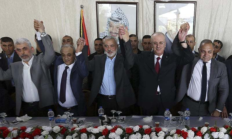 Hamas leader in the Gaza Strip Yahya Sinwar, Head of Palestinian General Intelligence Majid Faraj, Head of the Hamas political bureau Ismail Haniyeh, Palestinian Prime Minister Rami Hamdallah and an Egyptian mediator hold their hands up during a meeting in Gaza City.─AFP