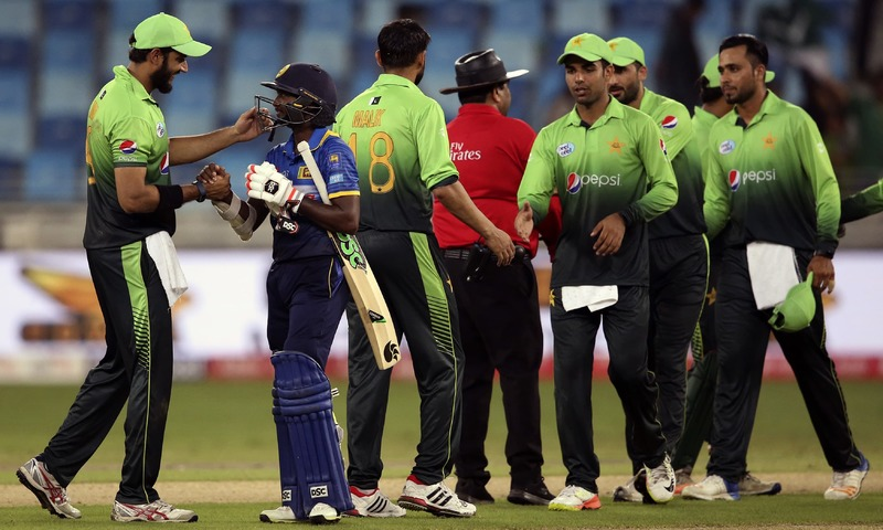 Imad Wasim shakes hands with Akila Dananjaya as the others celebrate after winning their first ODI against Sri Lanka in Dubai. —AP