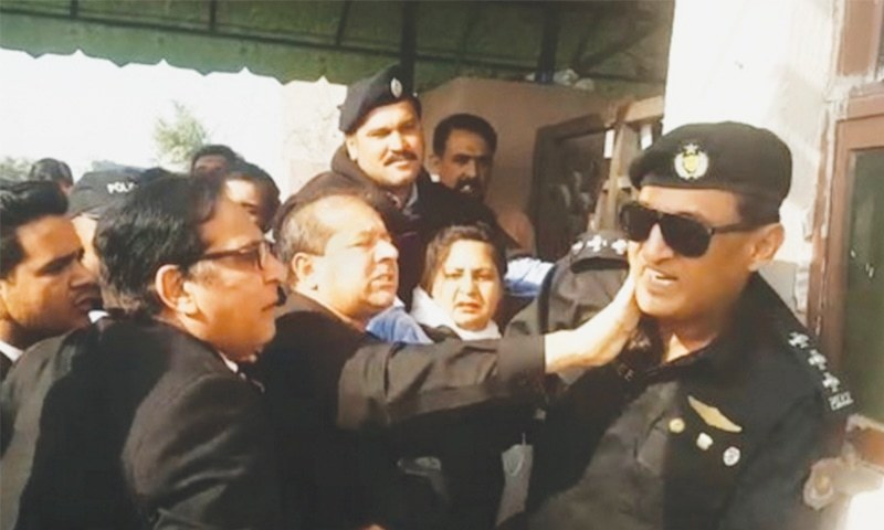 ISLAMABAD: A lawyer hits a police official deployed at the entrance of the accountability court to keep the crowd away.—Dawn