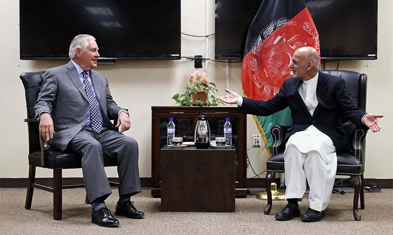 US Secretary of State Rex Tillerson talks to Afghan President Ashraf Ghani at Bagram Air Field on Monday. —AFP