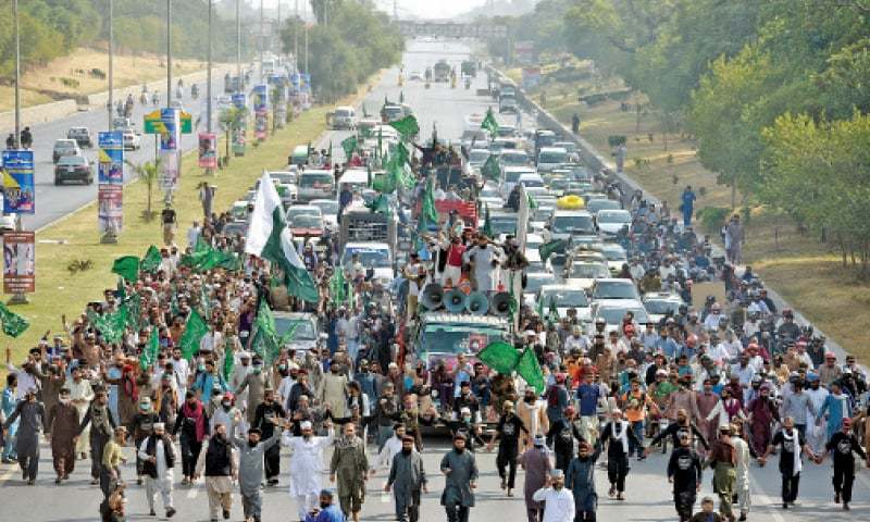 Participants of TLP's rally march down the Islamabad Expressway on Thursday. —Photo by Tanveer Shahzad