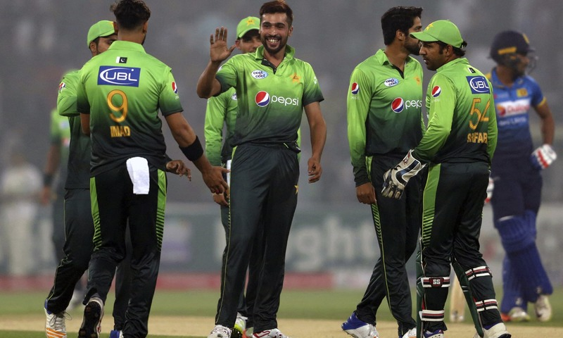 Mohammad Amir celebrates with teammates after taking the wicket of Dilshan Munaweera. —AP