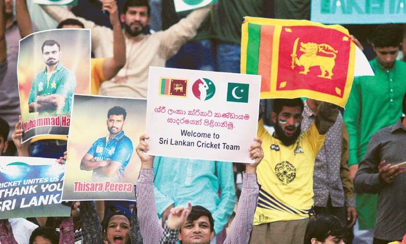 SPECTATORS hold placards during the Twenty20 international match between Pakistan and Sri Lanka  at the Gaddafi Stadium on Sunday.—Reuters