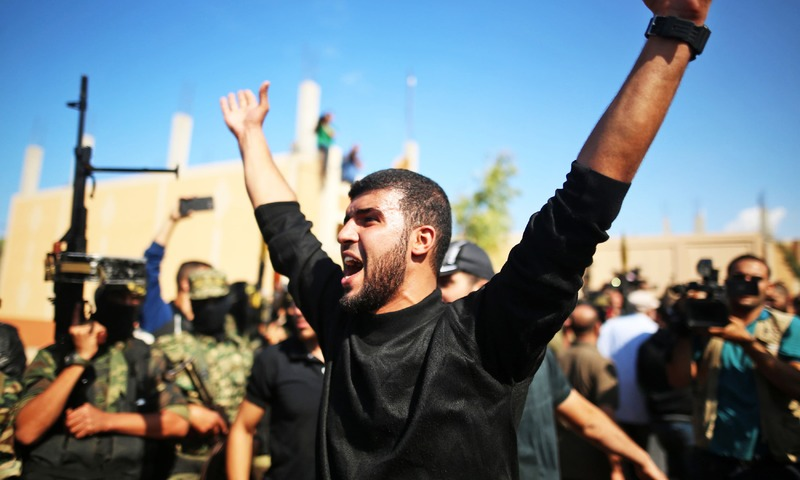 A mourner reacts as Palestinian Islamic Jihad militants hold their weapons during the funeral of their comrades killed in an Israeli operation to blow up a tunnel stretching from the Gaza Strip into Israel, in Nuseirat in the central Gaza Strip on October 31, 2017. —AFP