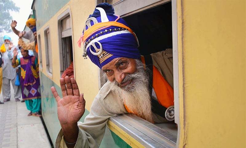 Sikh yatrees wave upon their arrival at Wagah Railway Station. — Online
